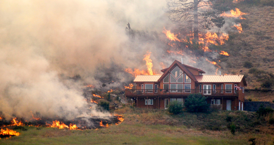 Wildfire spreading across a hillside right next to a house