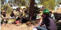 field crew sitting under a tree